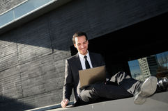 A businessman sitting on the floor with a laptop computer, risin Stock Images
