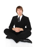 Businessman sitting on the floor and meditating Stock Image