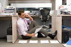 Businessman sitting on floor by piles of paperwork, using telephone, side view Stock Image