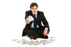Businessman sitting on floor surrounded by money Stock Images