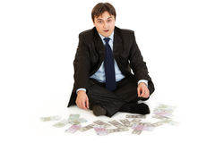 Businessman sitting on floor surrounded by money Royalty Free Stock Photos