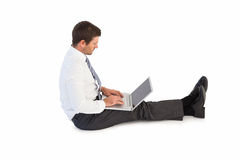 Businessman sitting on the floor typing on his laptop Royalty Free Stock Photos