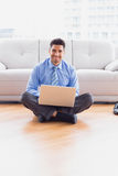 Businessman sitting on floor using his laptop smiling at camera Stock Photography