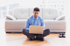Businessman sitting on floor using laptop Stock Photo