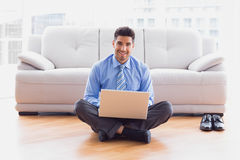 Businessman sitting on floor using laptop smiling at camera Stock Photography