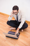 Businessman sitting on floor using mobile phone and laptop Royalty Free Stock Photos