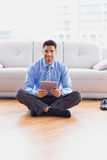 Businessman sitting on the floor using tablet smiling at camera Stock Photo