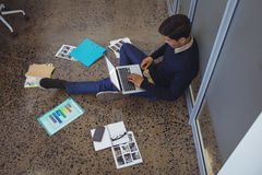 Businessman sitting on floor while working in creative office Stock Photos