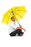 Businessman sitting on the floor with yellow umbrella Royalty Free Stock Photography