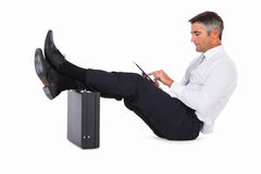 Businessman sitting with foot on briefcase and using tablet Royalty Free Stock Image