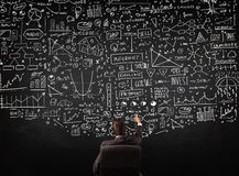 Businessman sitting in front of a blackboard with charts Royalty Free Stock Photo