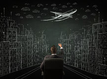 Businessman sitting in front of a cityscape drawing on a chalkbo Stock Photos