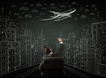 Businessman sitting in front of a cityscape drawing on a chalkbo Stock Images