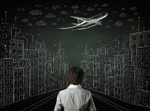 Businessman sitting in front of a cityscape drawing on a chalkbo Stock Photography