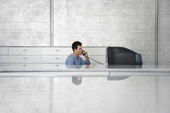 Businessman Sitting In Front Of Computer Using Telephone Stock Images