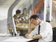 Businessman sitting in front of a desktop PC Royalty Free Stock Photography