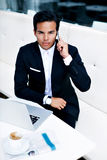 Businessman sitting front open laptop computer while having cell phone conversation in cafe Stock Photos