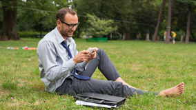 Businessman sitting on a grass and chatting on a cell phone with a happy expression. Stock Photo