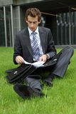 Businessman sitting on grass with documents Royalty Free Stock Photography