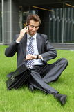 Businessman sitting on grass talking on cellphone Royalty Free Stock Photo
