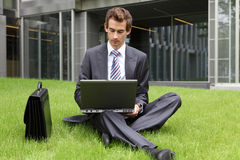 Businessman sitting on grass using his laptop Royalty Free Stock Images