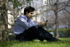 A businessman sitting on the grass, using his mobile phone Royalty Free Stock Photos
