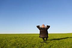 Businessman Sitting On Green Grassland Royalty Free Stock Photography