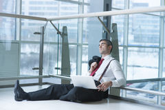 Businessman sitting on ground asleep with laptop Stock Photos