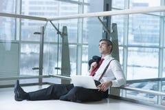 Businessman sitting on ground asleep with laptop Stock Photos