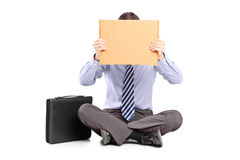 Businessman sitting on ground and hiding his face with a piece o Stock Photography