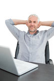 Businessman sitting with hands behind head with laptop Stock Images