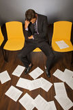 Businessman sitting with head in hands, documents scattered on floor Stock Photo