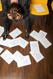 Businessman sitting with head in hands, documents scattered on floor Royalty Free Stock Image