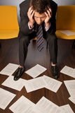 Businessman sitting with head in hands looking at documents scattered on floor Royalty Free Stock Photo