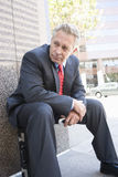 Businessman Sitting On His Briefcase Royalty Free Stock Photography