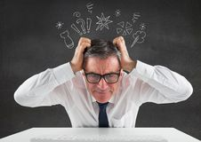 Businessman sitting on his desk with hands on his head against thinking icons in background Royalty Free Stock Photos