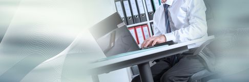 Businessman sitting at his desk; panoramic banner. Businessman sitting at his desk and working on laptop; panoramic banner stock photography