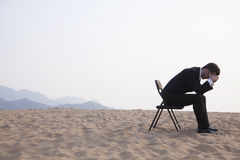 Businessman sitting with his head in his hands in the middle of the desert royalty free stock photos
