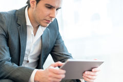 Businessman sitting in his office as he looks at  his tablet com Royalty Free Stock Photography