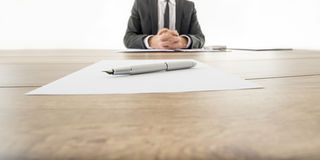 Businessman sitting at his wooden office desk with contract infr Royalty Free Stock Photo