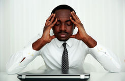 Businessman sitting at his workplace. Pensive african businessman sitting at his workplace in office Royalty Free Stock Images