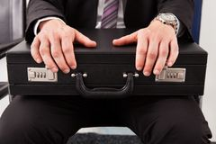 Businessman sitting and holding briefcase Stock Photo