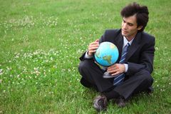 Businessman sitting and holding globe Royalty Free Stock Photography