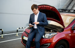 Businessman sitting on hood of broken car and searching how to f Stock Photo
