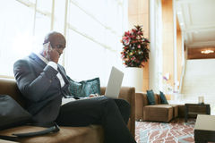Businessman sitting in hotel lobby using cell phone and laptop Stock Photos