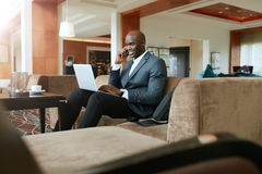 Businessman sitting in hotel lobby using cell phone and laptop Royalty Free Stock Photo