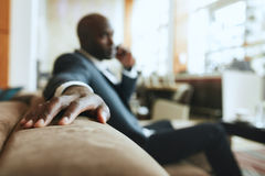 Businessman sitting in hotel lobby using cell phone and laptop. Businessman sitting on sofa working using cell phone and laptop. African male executive waiting Royalty Free Stock Photo