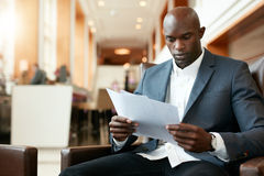 Businessman sitting in hotel lobby using cell phone and laptop. Businessman sitting on sofa working using cell phone and laptop. African male executive waiting Stock Image