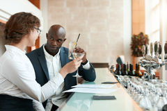 Businessman sitting in hotel lobby using cell phone and laptop Stock Photo