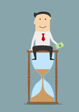 Businessman sitting on a hourglass with money Royalty Free Stock Image